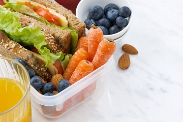 lunch box with sandwich of wholemeal bread on white background