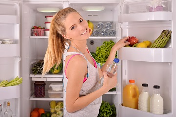 Young beautiful woman standing in the refrigerator door in fitness clothes and drinking water from a bottle while looking at the camera and smiling.