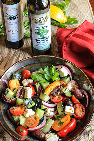 Greek Salad with Baby Heirloom Tomatoes and an Oregano Balsamic Vinaigrette featuring Sigona's Garlic Oil and Oregano White Balsamic Vinegar.