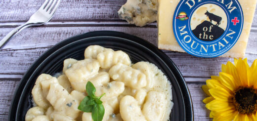 Carmelo's Homemade Gnocchi with a Dream of the Mountain and Dolce Gorgonzola Cheese Sauce Homemade gnocchi doesn't need to be intimidating! You may need to experiment with a potato-flour ratio before you get it just right, but once you get the hang of it you'll make gnocchi all the time! Dream of the Mountain is a xxxx-type cheese that our cheese buyer, John Nava, brought over from Switzerland JUST for Sigona's. He met the maker and even named this cheese while in Switzerland, so it is exceptionally special. It melts well and creates a lovely sauce. Adding a little dolce gorgonzola adds a fantastic, rich flavor and creamy texture. If you want to try the gnocchi without a cheese sauce, see an alternative serving suggestion below. Gnocchi: • Two medium-large russet potatoes • Salt and pepper, to taste • 1 large egg • 1/4 cup shredded Dream of the Mountain cheese • 1 cup, plus at least 1/2 cup more, flour Cheese Sauce: • 2 to 3 Tbsp butter • 4 fresh sage leaves • 1/4 cup milk • 1/4 cup heavy cream • 1/2 cup shredded Dream of the Mountain cheese • 1/2 cup crumbled or lightly packed Dolce Gorgonzola cheese Sauce-less Option: • A couple tablespoons olive oil • 8 to 10 fresh sage leaves Directions: Either boil the potatoes until fork tender (about 20-30 minutes) or prick the skin of the potatoes and bake at 350°F for an hour. While they're still warm, scoop out the potato and discard the skin. Run the potato through a ricer or use a masher to mash the potatoes. Make a well in the potatoes and add the egg, cheese, salt and pepper. Mix together with a fork. Make a mound of 1 cup of flour on a large cutting board; keep the remaining flour nearby. Turn out the potato mixture out on top of the flour. Use your hands to kneed the mixture together until a dough forms. If it is sticky, add more flour as needed. Roll the dough into a rounded mound and divide into 4 equal portions. Using one portion at a time, roll out the dough into a long rope, aiming for about a ½ to 1 inch diameter (cut the rope in half if it becomes too long). Slice the rope into pieces about 1 inch long and set aside; make sure the new surface is well floured. Optional: to give the gnocchi an artistic touch, place a for on the work surface and gently side each gnocchi over the fork prongs to make a decorative shape. The ribs on the gnocchi help the sauce adhere better for a deliciously saucy bite. Place the gnocchi on a sheet pan and place in the freezer while infusing the butter preparing the cheese sauce. Set a pot of salted water to boil. In a large skillet, melt the butter with the sage leaves over medium-low heat. Once melted, add the milk and heavy cream; when warmed through, add the cheeses and stir continuously as the cheese melts. Remove the sage. While the cheese is melting, add the gnocchi to the boiling water, working in batches if necessary. As the gnocchi float to the top, use a round mesh skimmer to remove from the water and stir into the cheese sauce (continue to stir the cheese sauce). Once all the cheese is melted and the sauce is smooth, you can remove the sauce from the heat. Serve the gnocchi while warm. Sauce-less option: Heat a couple tablespoons of olive oil over medium-high heat. Add about 10 sage leaves and allow to cook and infuse the oil with flavor. Meanwhile, boil the gnocchi as directed above. Remove to a paper or other towel and pat dry. Add the dried gnocchi to the hot oil and sear on both sides until lightly browned and slightly crisp. Serve with the seared sage leaves.