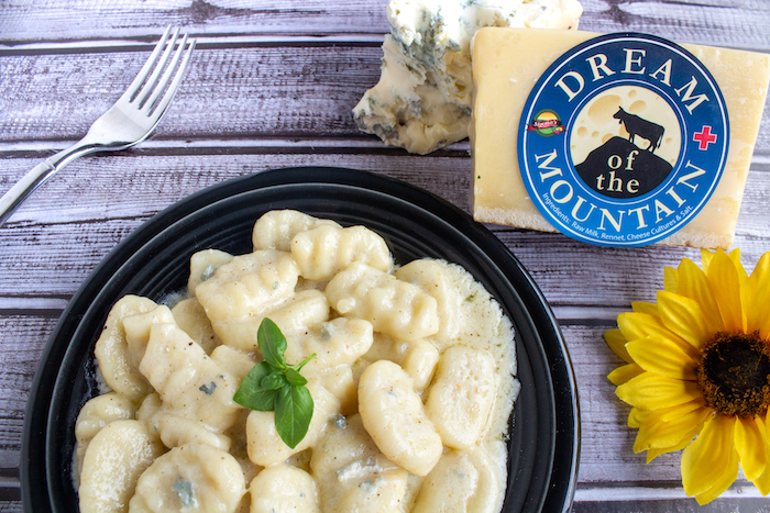 Carmelo's Homemade Gnocchi with a Dream of the Mountain and Dolce Gorgonzola Cheese Sauce Homemade gnocchi doesn't need to be intimidating! You may need to experiment with a potato-flour ratio before you get it just right, but once you get the hang of it you'll make gnocchi all the time! Dream of the Mountain is a xxxx-type cheese that our cheese buyer, John Nava, brought over from Switzerland JUST for Sigona's. He met the maker and even named this cheese while in Switzerland, so it is exceptionally special. It melts well and creates a lovely sauce. Adding a little dolce gorgonzola adds a fantastic, rich flavor and creamy texture. If you want to try the gnocchi without a cheese sauce, see an alternative serving suggestion below. Gnocchi: • Two medium-large russet potatoes • Salt and pepper, to taste • 1 large egg • 1/4 cup shredded Dream of the Mountain cheese • 1 cup, plus at least 1/2 cup more, flour Cheese Sauce: • 2 to 3 Tbsp butter • 4 fresh sage leaves • 1/4 cup milk • 1/4 cup heavy cream • 1/2 cup shredded Dream of the Mountain cheese • 1/2 cup crumbled or lightly packed Dolce Gorgonzola cheese Sauce-less Option: • A couple tablespoons olive oil • 8 to 10 fresh sage leaves Directions: Either boil the potatoes until fork tender (about 20-30 minutes) or prick the skin of the potatoes and bake at 350°F for an hour. While they're still warm, scoop out the potato and discard the skin. Run the potato through a ricer or use a masher to mash the potatoes. Make a well in the potatoes and add the egg, cheese, salt and pepper. Mix together with a fork. Make a mound of 1 cup of flour on a large cutting board; keep the remaining flour nearby. Turn out the potato mixture out on top of the flour. Use your hands to kneed the mixture together until a dough forms. If it is sticky, add more flour as needed. Roll the dough into a rounded mound and divide into 4 equal portions. Using one portion at a time, roll out the dough into a long rope, aiming for about a ½ to 1 inch diamet
